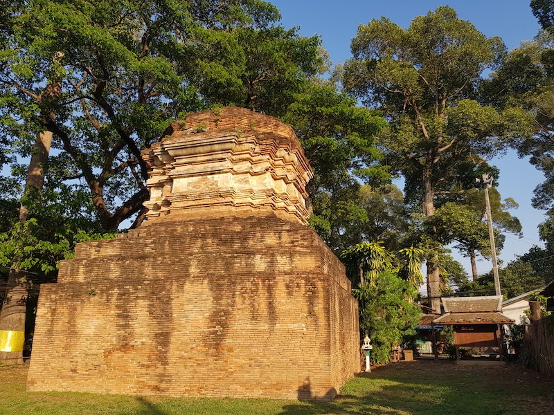 Old ruined chedi with tall trees