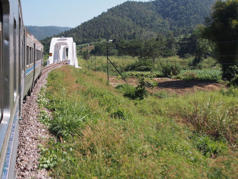Train approaching bridge with mountains in the background