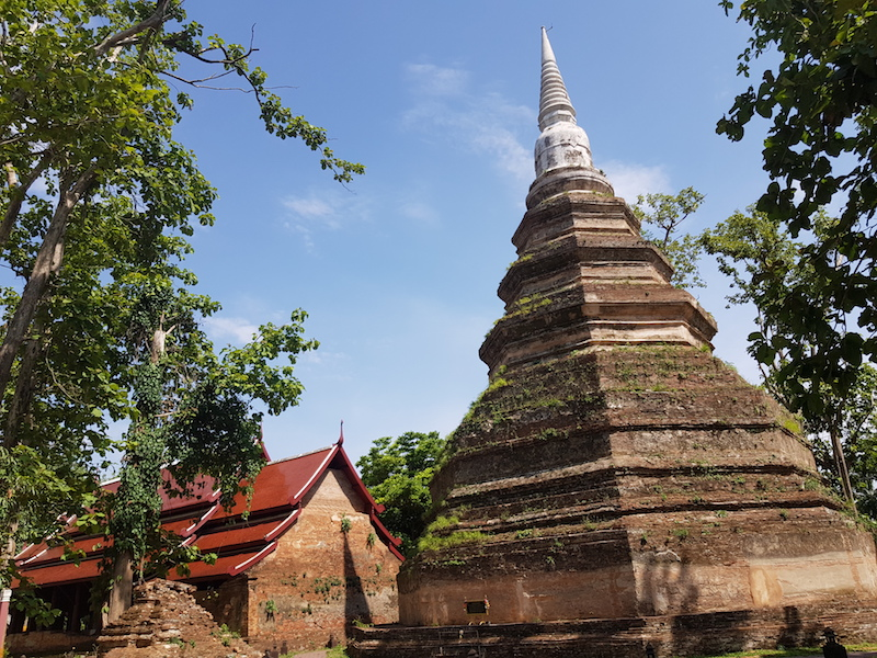 Ruined chedi with temple building