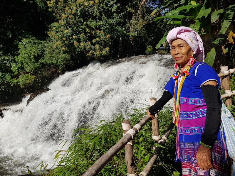 Woman in tribal dress at a waterfall
