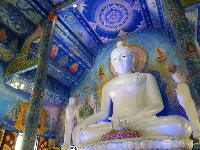 White Buddha statue with blue background