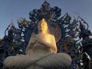 White Buddha statue against blue background